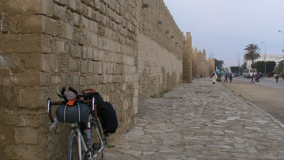 The walls of Monastir prop up Vin Cox's bike on day 9 of the world tour.