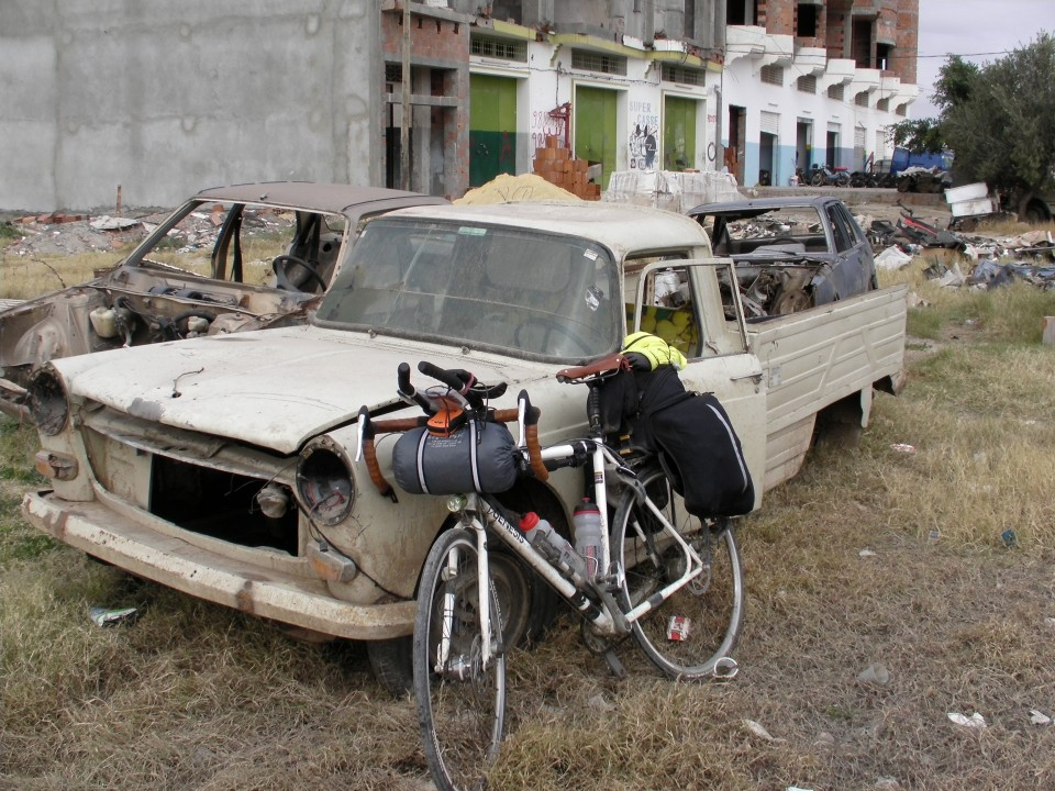 Vin Cox's Criox de Fer bike resting against a rusty truck in Tunisia.