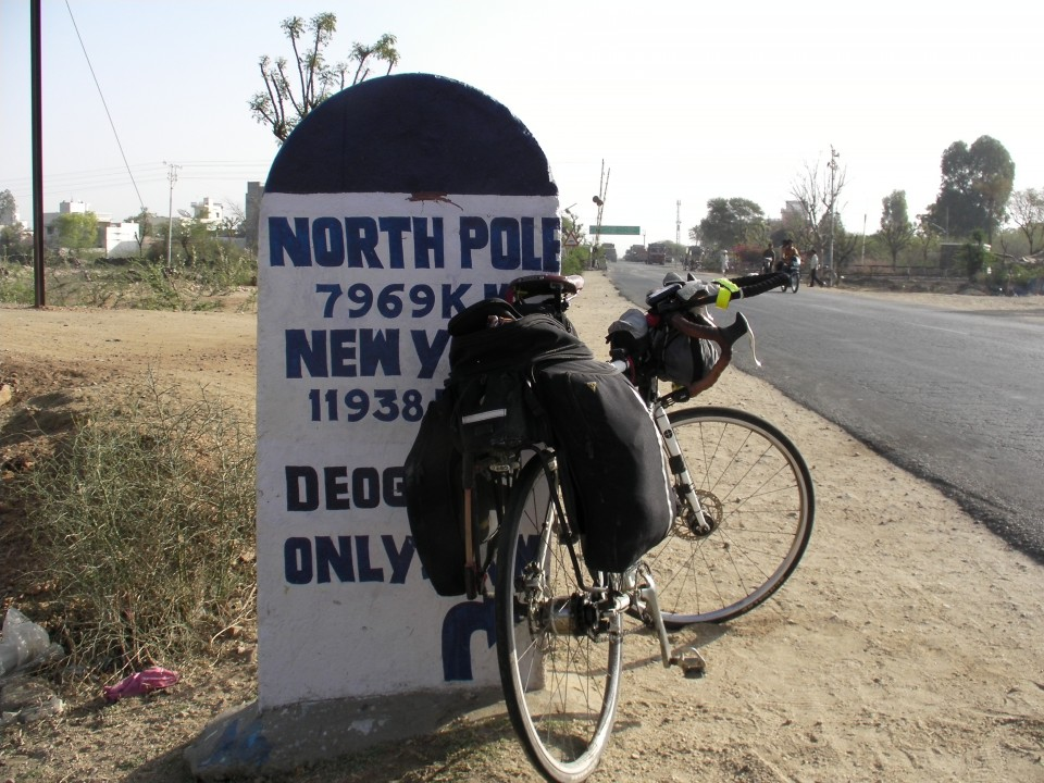 Vin Cox's Genesis bike leans against a helpful milepost in India.